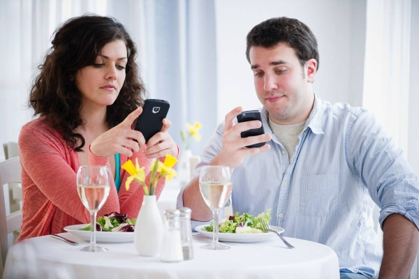 Jersey City, New Jersey, USA --- USA, New Jersey, Jersey City, Couple having dinner and text messaging  --- Image by © Jamie Grill/Tetra Images/Corbis